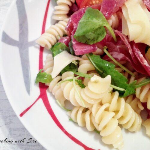 In una ciotola tagliate a pezzetti la bresaola, le fettine del Leerdammer e mettete al piatto un po' di rucola, aggiungete la pasta fredda e condite con un filo d'olio.